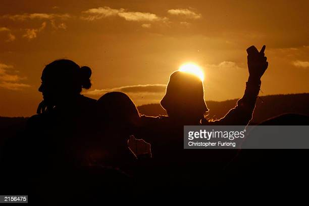 Music lovers watch the sun go down during The T In The Park Festival on July 12 2003 at Balado near Kinross in Scotland