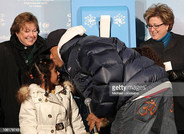 Music mogul Russell Simmons kisses his daughter Aoki Lee as UNICEF Executive Director Ann Veneman and UNICEF President and CEO Carol Ster look on...