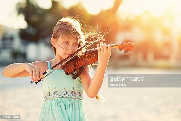 music of the summer - girl playing violin on beach - imgorthand stock photos and pictures
