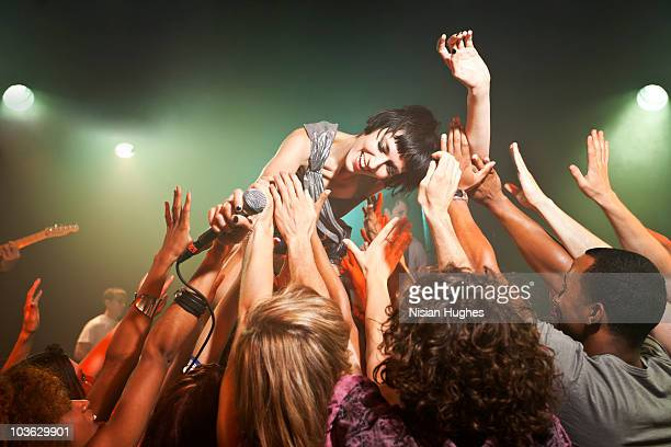Music performer crowd surfing