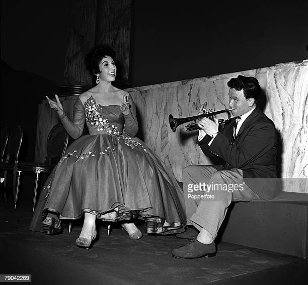 1955 British singer Alma Cogan is pictured listening as Freddie Randall plays his trumpet