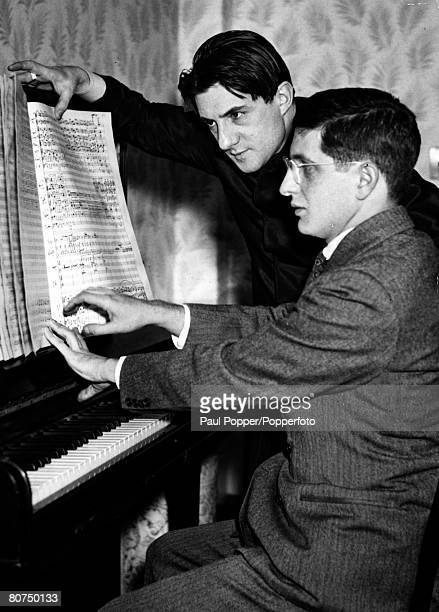 circa 1940's John Barbirolli celebrated English conductor pictured as he looks over a music score with the youthful composer Bernard Hermann at the...