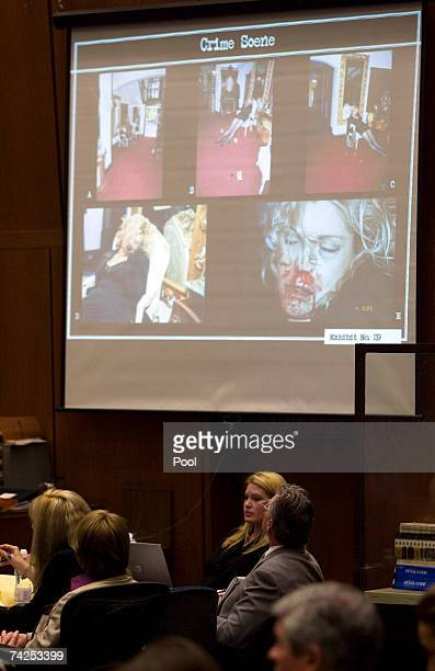 Music producer Phil Spector sits with his defense team as a photos showing the position of the body of actress Lana Clarkson are projected inside the...