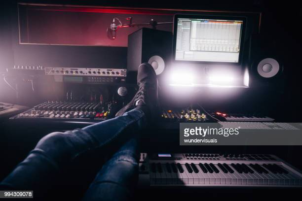 music producer relaxing with feet up in music recording studio - post-production stock pictures, royalty-free photos & images