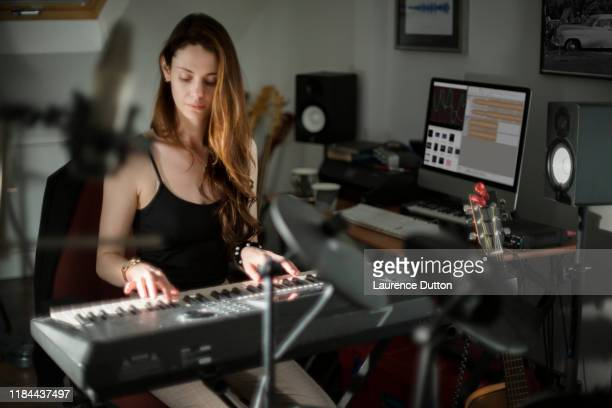 音楽制作キーボード女性 - シンガーソングライター ストックフォトと画像