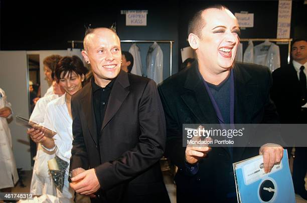 Music stars Keith Flint and Boy George guests of honor of Versace's spring/summer event joking and laughing in the backstage among the people at work...