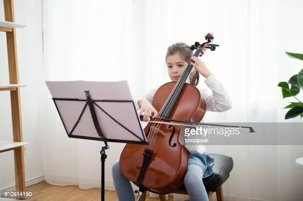 music student girl playing cello at home - cello stock pictures, royalty-free photos & images