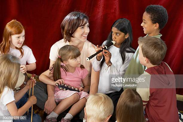music teacher and young students (4-9) rehearsing on stage, smiling - recorder musical instrument stock photos and pictures