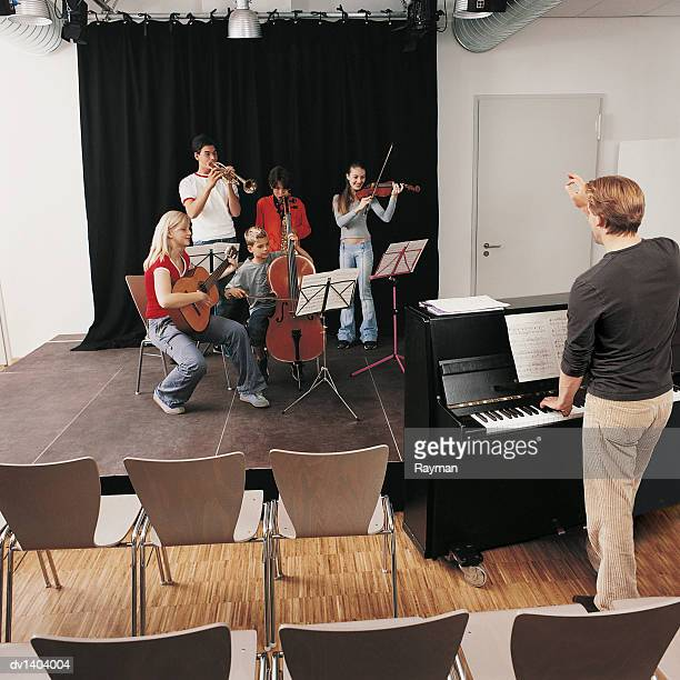 Music Teacher Conducts a Band of School Children Playing Instruments