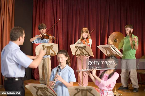 Music teacher instructing school orchestra