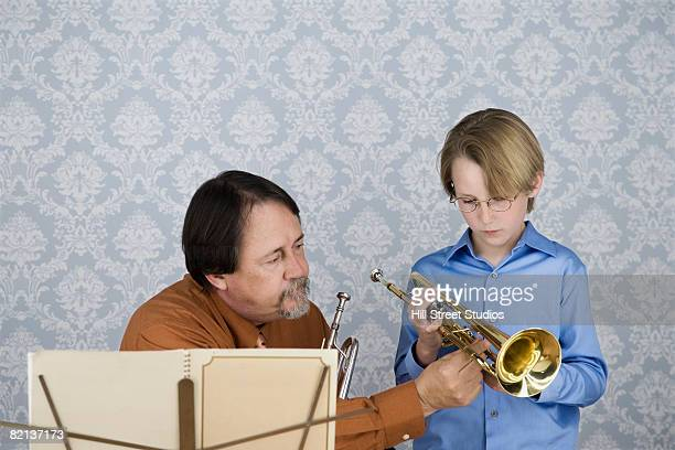Music teacher teaching boy to play trumpet