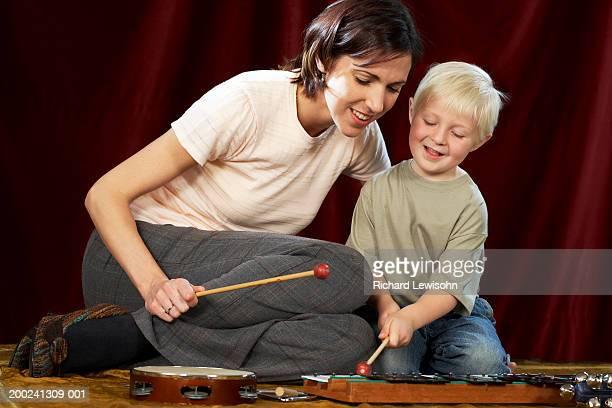 Music teacher watching boy (3-5) play xylophone, smiling