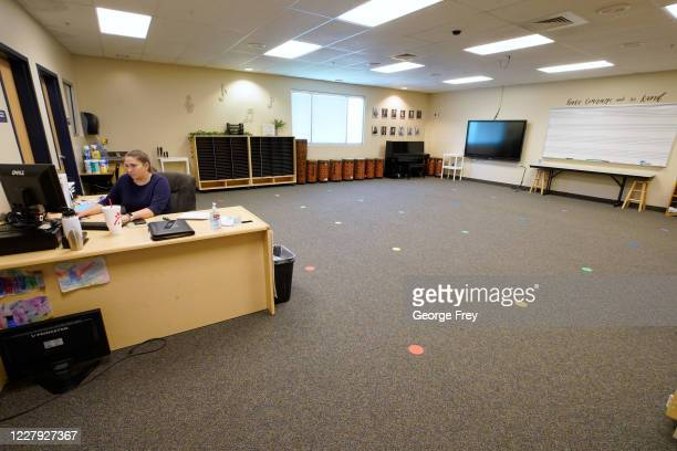 A music teacher works at her desk as dots mark spots for new rules on social distancing at Freedom Preparatory Academy as they begin to prepare to...