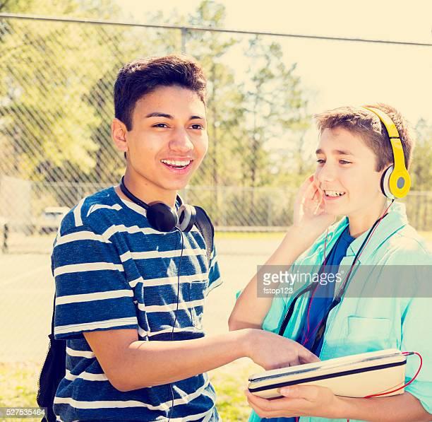 Music: Teenage boy friends with headphones, digital tablet at park.