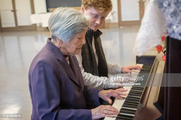 music therapy, senior asian woman playing piano with young man - keyboard player stock photos and pictures