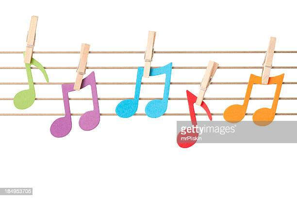 musical notes pegged to string stave - musical note stock photos and pictures