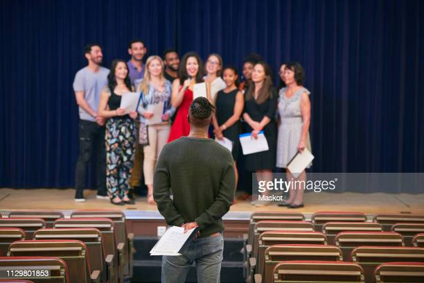 musical teacher listening to choir on stage in auditorium of language school - rehearsal stock pictures, royalty-free photos & images