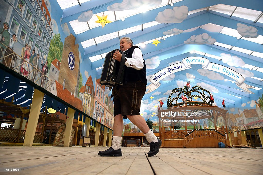 A musican walks through the Hacker Festzelt during the official 2013 Oktoberfest one-liter beer glass presentation weeks ahead of Oktoberfest on August 27, 2013 in Munich, Germany. Munich Oktoberfest, which opens to the public on September 21, draws millions of visitors and is the biggest beer fest in the world.