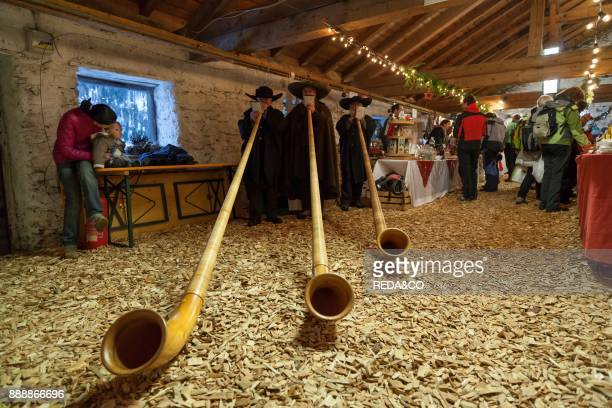 Musicans In Traditional Garment Playing The Alphorn Or Alpenhorn On A Christmas Market In Martell Valley Europe Central Europe Italy South Tyrol...