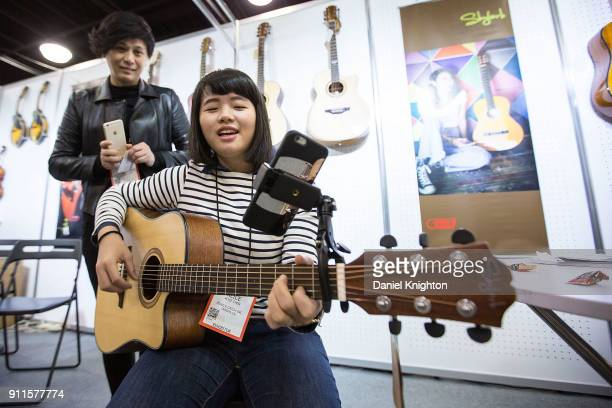 Musician Alice Chen demonstrates the Mobile Catch mobile phone holder at The 2018 NAMM Show at Anaheim Convention Center on January 28 2018 in...