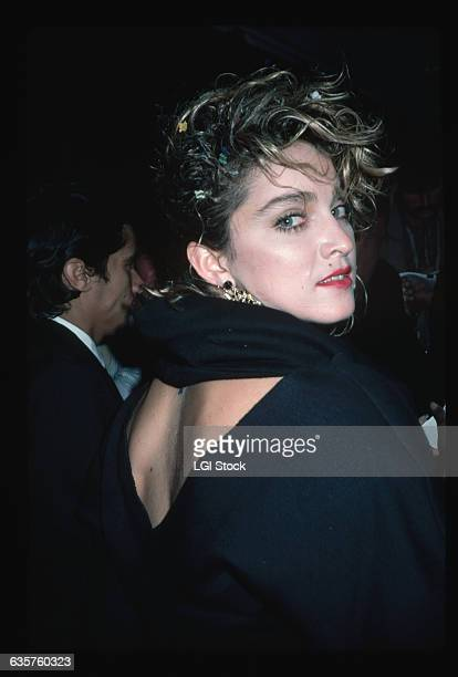 Musician and actress Madonna looks over her shoulder while wearing a backless dress
