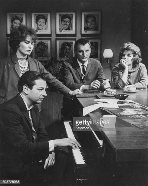 Musician and conductor Andre Previn playing the piano watched by Dory Langdon Julie London and Bobby Tramp circa 1970