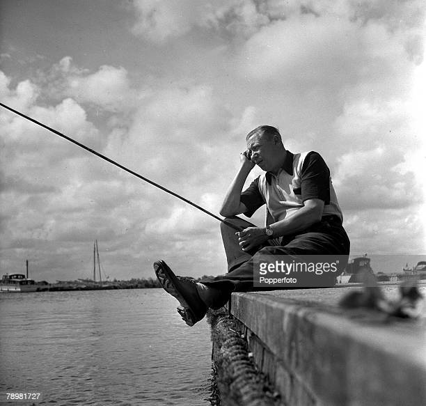 1952 Musician and film star George Formby relaxing as he fishes