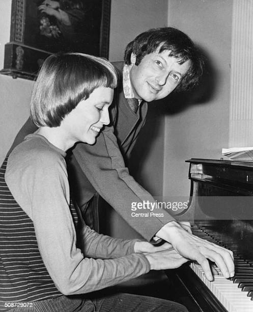 Musician Andre Previn and his wife actress Mia Farrow playing the piano together during rehearsals for a performance of 'Joan of Arc at the Stake' at...