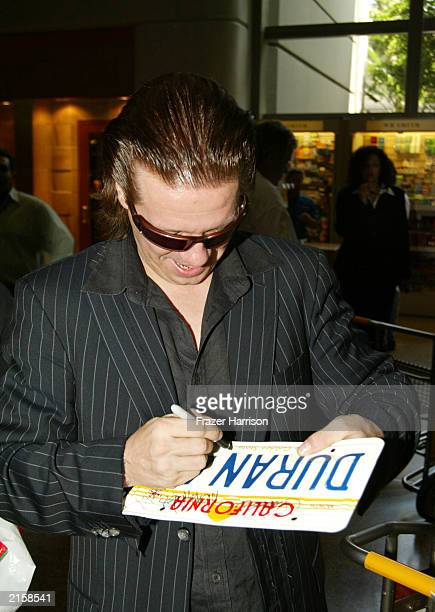 Musician Andy Taylor of Duran Duran signs autographs at Los Angeles International airport after arriving from Japan on July 13 2003 in Los Angeles...