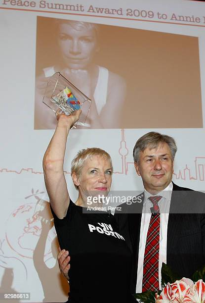 Musician Annie Lennox holds up a piece of the Berlin historical wall that she get from Berlin's mayor Klaus Wowereit after she received the Peace...