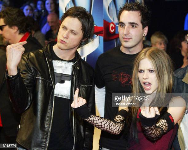 Musician Avril Lavigne gestures with members of her band as they arrive for the JUNO Awards ceremony at the Rexall Centre April 4 2004 in Edmonton...