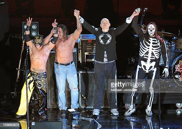 Musician Billy Corgan of the Smashing Pumpkins poses with Mexican wrestlers during the 2010 MTV World Stages concert at the Auditorio Nacional on...