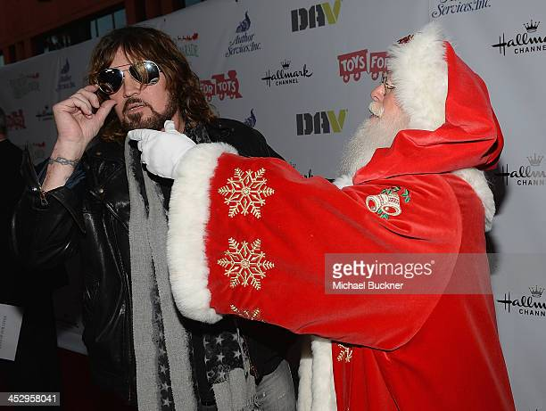 Musician Billy Ray Cyrus and a man dressed a Santa Claus arrive at the 82nd Annual Hollywood Christmas Parade on Hollywood Blvd on December 1 2013 in...