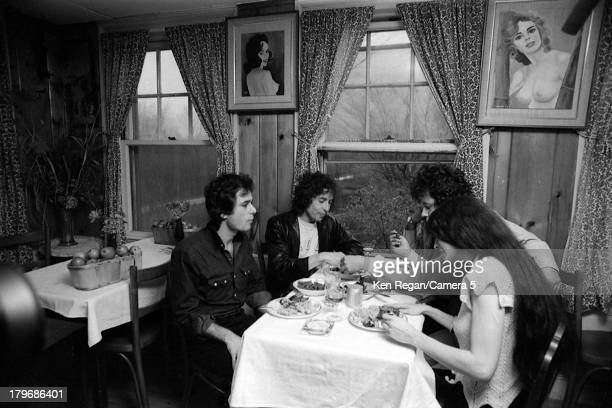 Musician Bob Dylan is photographed eating with friends at Dream Away Lodge during the Rolling Thunder Revue in November 1975 in Stockbridge...