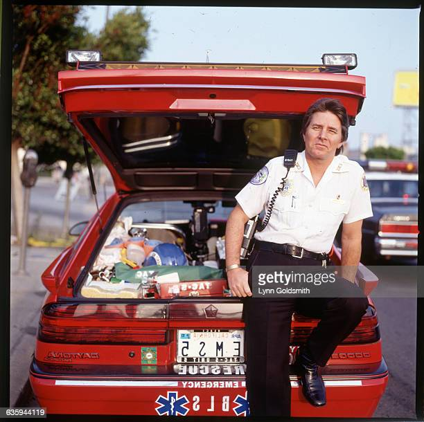 Musician Bobby Sherman dressed as a paramedic stands near an emergency vehicle