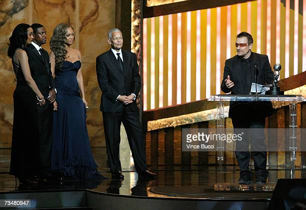 """Musician Bono accepts the """"Chairman's Award"""" from from actor Chris Tucker, model/TV Host Tyra Banks, and NAACP Chairman Julian Bond onstage during..."""