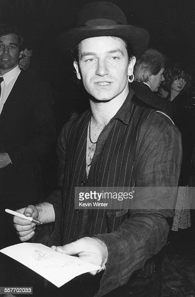 Musician Bono, leader singer of the band 'U2', signing autographs for fans, circa 1988.