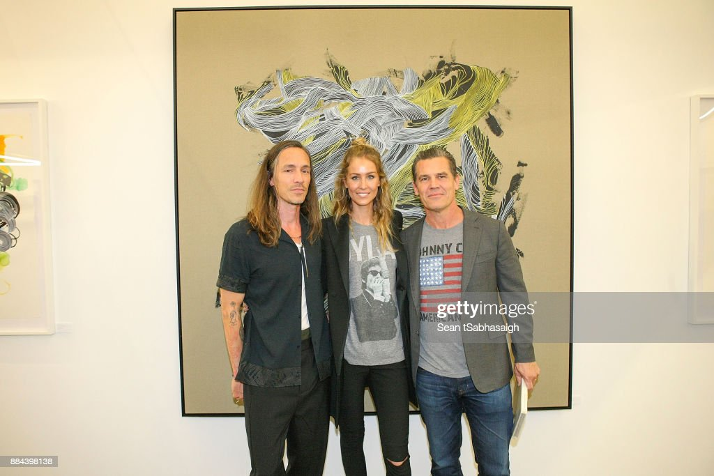 Musician Brandon Boyd (L), Kathryn Boyd (Ct) and Josh Brolin pose in front of a Brandon Boyd artwork while at OptiMystic: A Brandon Boyd Pop Up Gallery Featuring He, Tasya Van Ree, Natalie Bergman, Diana Garcia And DJ Set By Brent Bolthouse at 101/Exhibit Gallery on December 1, 2017 in West Hollywood, California.