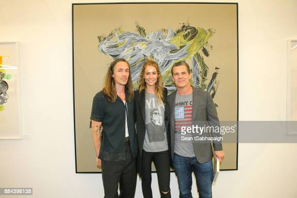 Musician Brandon Boyd Kathryn Boyd and Josh Brolin pose in front of a Brandon Boyd artwork while at OptiMystic A Brandon Boyd Pop Up Gallery...