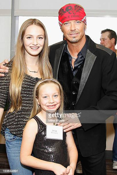 Musician Bret Michaels poses with daughters Raine Sychak and Jorja Sychak during the ribbon cutting ceremony for the new Bret Michael's Hospitality...