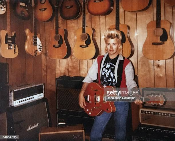 Musician Brian Setzer of Stray Cats poses for a portrait on Polaroid film with a guitar in front of a wall of guitars and amps including a Marshall...