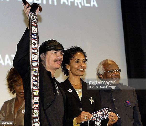 Musician Carlos Santana and his wife Deborah display their presents offered by South African craftmen as South African Archbishop Desmond Tutu looks...