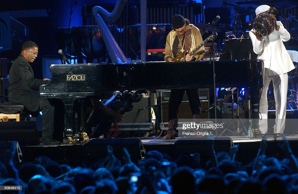Musician Carlos Santana (R) and musician Herbie Hancock perform on stage at the 'We are the Future' all-star humanitarian concert May 16, 2004 at Circus Maximus in Rome, Italy. The show is being broadcast globally on MTV and will raise money to open child centers in the most war torn regions of the world.
