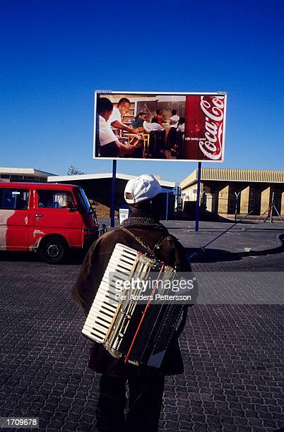 Musician carries an accordion after playing on the street on August 10, 2001 in Site C Khayelitsha, a township about 35 kilometers outside Cape Town,...