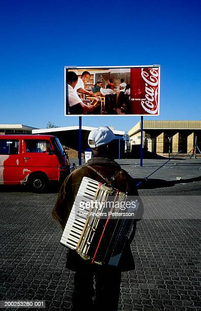 Musician carries an accordion in Khayelitsha, South Africa