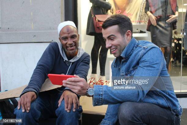 Musician Chris Leamy shows the homeless Hassan Ali an Instagram post in New York US 28 September 2016 Leamy wants to help the homeless and make them...