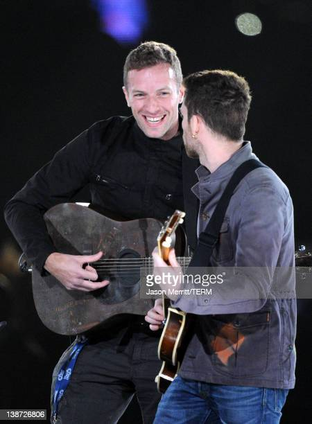 Musician Chris Martin and Guy Berryman of the band Coldplay performs onstage at the 2012 MusiCares Person of the Year Tribute to Paul McCartney held...