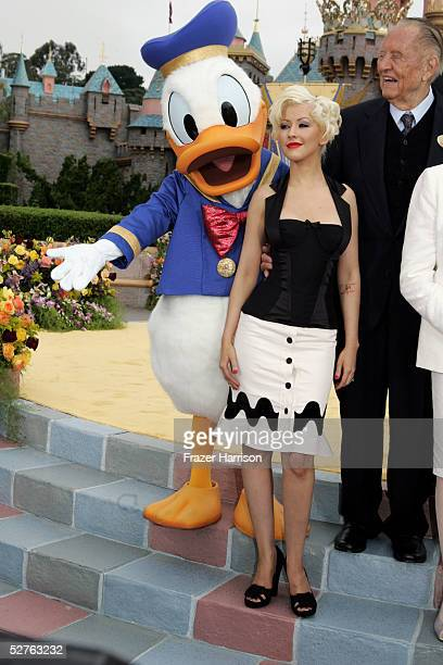 Musician Christine Aguilera and Donald Duck pose in front of the Sleeping Beauty Castle after launching the Happist Celebration on Earth during the...
