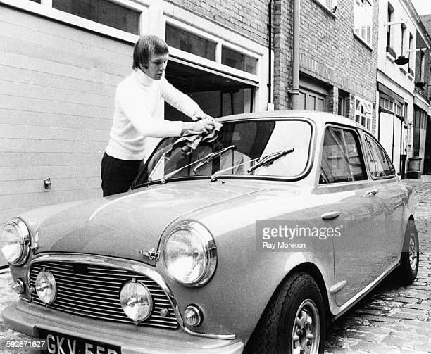 Musician Colin Petersen drummer with the band the 'Bee Gees' wiping the window of his car outside his mews flat in Bayswater London circa 1970