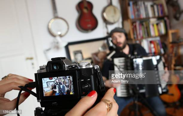 Musician Daniel Kahn plays accordion and sings as his wife and camera operator Yeva Lapsker uses a video camera to livestream his performance from...